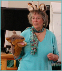 Peggy demonstrates the use of giraffe ears and jackal puppet during a Level 1 training
